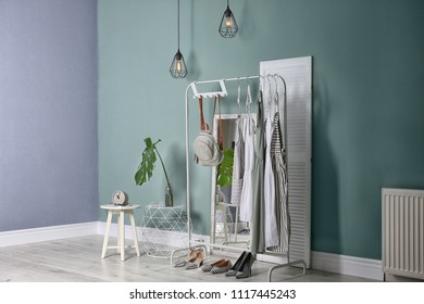 Stylish dressing room interior with clothes on rack