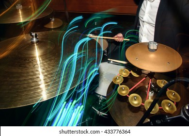stylish drummer playing on a drums with a band on wedding reception with cool motion light
