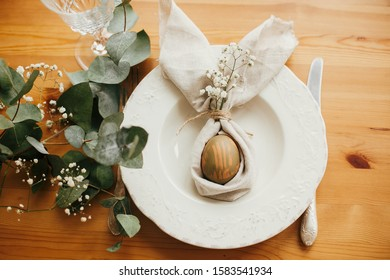 Stylish Easter brunch table setting with egg in easter bunny napkin. Modern natural dyed green egg on napkin with bunny ears, flowers on vintage plate and cutlery. Easter table decorations