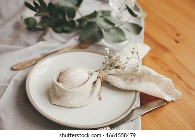 Stylish Easter brunch table setting with egg in easter bunny napkin on  table. Modern natural dyed pink easter egg on napkin with bunny ears, flowers on plate and cutlery. Easter table decorations
