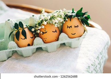 Stylish easter eggs in floral wreath and sleeping cute faces in carton tray on wooden background. Modern cute easter eggs with flowers crown in sunny light. Happy Easter, eco concept. Space for text