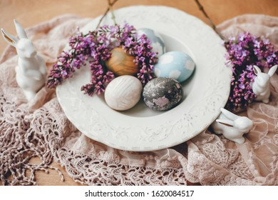 Stylish Easter eggs on vintage plate, white bunnies and lilac flowers on fabric on wooden table. Rural composition of colorful natural dyed easter eggs and spring flowers. Holiday decor