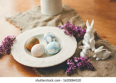 Stylish Easter eggs on vintage plate, white bunny rabbits and lilac flowers on rustic fabric on wooden table. Rural easter composition of natural dyed eggs and spring purple flowers