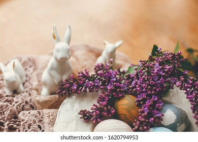 Stylish Easter eggs on vintage plate, white bunnies and lilac flowers on fabric on wooden table. Rural  natural dyed easter eggs and spring flowers. Space for text. Holiday decor