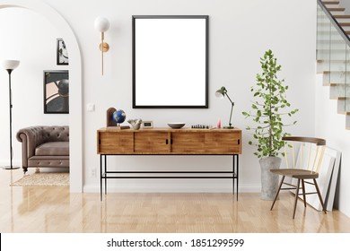 Stylish and eclectic dining room interior with mock up poster map, sharing table design chairs, gold pedant lamp and elegant sofa in second space. White walls, wooden parquet. Tropical leafs in vase.