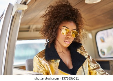 stylish edgy african american woman wearing golden jacket and sunglasses in old van