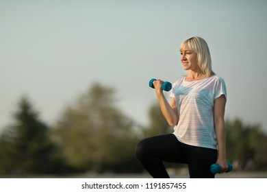 stylish elderly woman exercising with dumbbells in summer in the park against the sky
