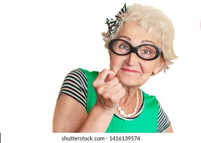 Stylish elderly woman hipster  with an evil face shows a fig. Concept protest and objection of an old woman. Isolated