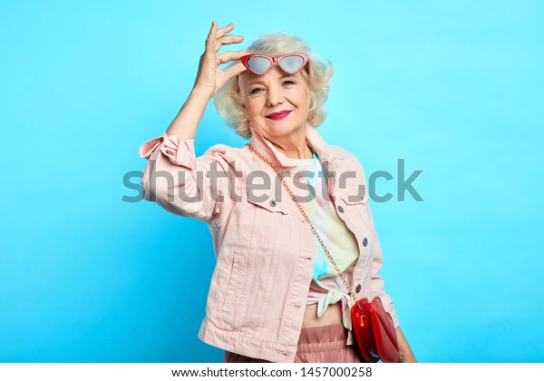Stylish elderly woman in sunglasses and trendy clothes is smiling and looking at the camera. happiness, beuty, free time, spare time