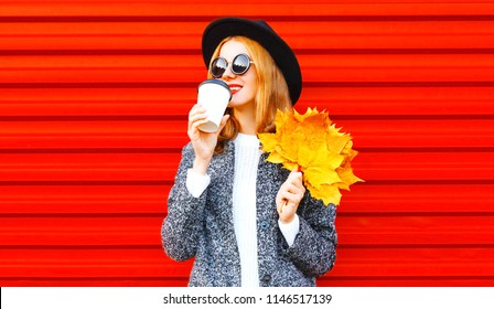 Stylish elegant autumn woman drinks coffee holds yellow maple leaves on red background