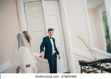 A stylish elegant bride dancing with groom stands on stairs with railing with patterns near doors. Close up. Portrait. Retro. Vintage architecture indoors. forged metal staircase.