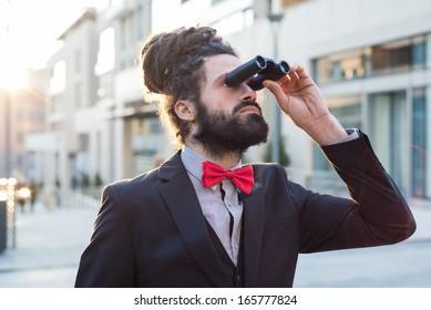 Stylish elegant dreadlocks businessman binoculars in business landscape