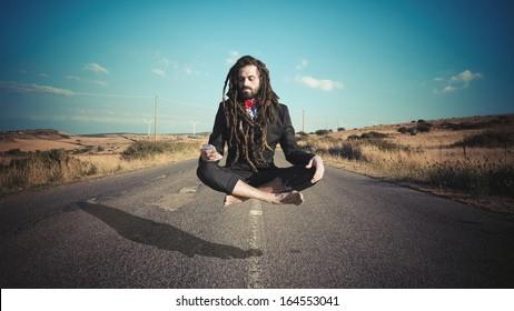 Stylish elegant dreadlocks businessman levitating in a desolate road