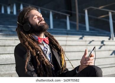 Stylish elegant dreadlocks businessman listening music in business landscape