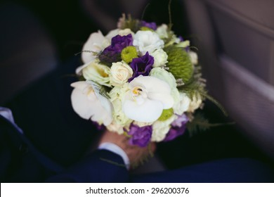 stylish elegant groom with bouquet on the background of luxury car in the city