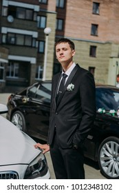 stylish elegant groom holding bouquet standing near car on the background of old city