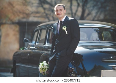 stylish elegant groom holding bouquet standing near old retro car on the background of old city