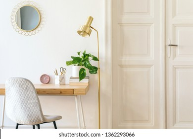 Stylish and elegant home interior with wooden desk, grey velvet chair, design accessories, gold lamp and hanging mirror on the white wall. Piece of design woman's room. White wooden door. Copy space.