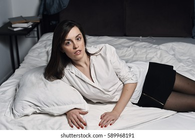 Stylish elegant lady lying in casual clothes on the bed in the bedroom