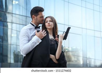 Stylish elegant man hugs a beautiful girl holding a gun in his hand, outside.