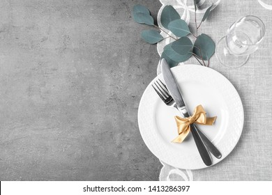 Stylish elegant table setting on grey background, top view. Space for text