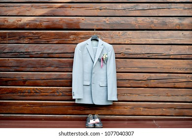 Stylish elegant wedding groom suit with buttonhole hanging on wooden background, copy space. Gray suit hangs above leather groom shoes and pink bowtie. Groom wedding accessories, free space