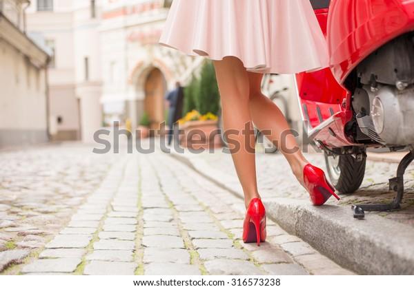 光る赤いモトスクーターの横にあるスタイリッシュでエレガントな女性