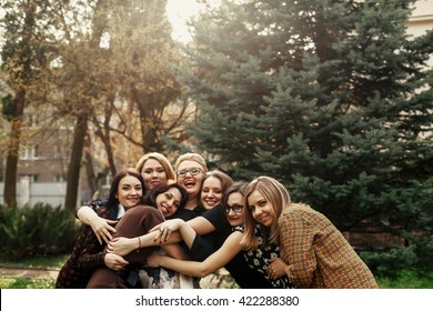 stylish elegant women having fun at celebration in sunny park, funny moment concept, gathering together