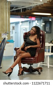 Stylish elegant young black woman posing in short trendy dress and heels while sitting in leather armchair