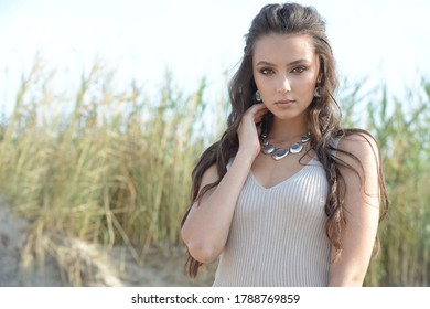 Stylish emotional girl in silver jewelry. Amazing curly brunette stands on the sand. Hair fluttering in the wind.