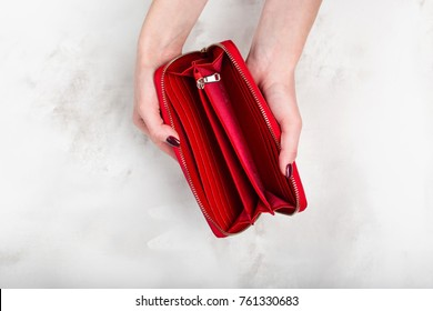Stylish empty female red purse in female hands on a white texture