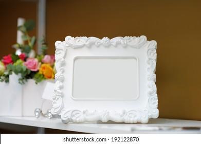 Stylish empty frame on a bookshelf