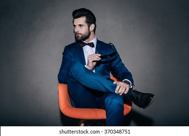 Stylish as ever. Young handsome man in suit holding his sunglasses and looking away while sitting in orange chair against grey background