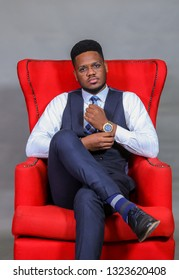 Stylish as ever. Young handsome Nigerian/African American man in waistcoat holding his arm, crossed legs, wearing transparent eyeglasses while sitting in a red arm chair against grey background.