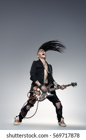 Stylish expressive rock musician is playing electrical guitar and shaking his hair. Full length studio shot. Entertainment and musical concept.