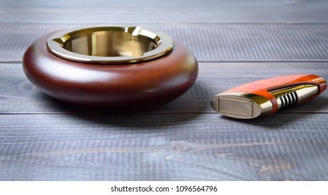 Stylish exquisite ashtray and lighters on a gray wooden background