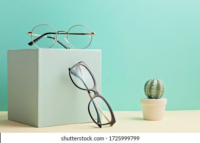 Stylish eyeglasses over pastel  background. Optical store, glasses selection, eye test, vision examination at optician, fashion accessories concept. Front view