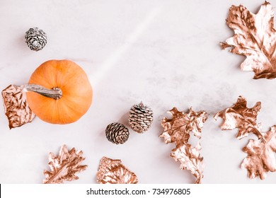 Stylish fall season flatlay on white marble background. Little pumkin, rose gold painted leaves. Copy space for text