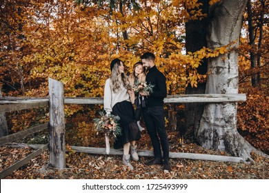 Stylish family in the autumn forest. A young guy and a girl are standing near a wooden fence and holding their daughter in their arms. Mom and daughter are holding bouquets of flowers