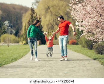 Stylish family couple of young pretty woman and handsome man walking in park with son on toy car sunny day near blooming trees