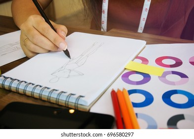 Stylish Fashion Designer work as sketch of new collection in atelier. Creative Design Concept.