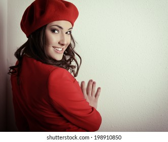 Stylish fashion girl in red suit and beret, posing at studio over white wall, toned