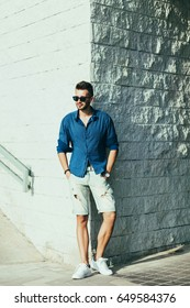 Stylish fashion man posing in shorts and shirt