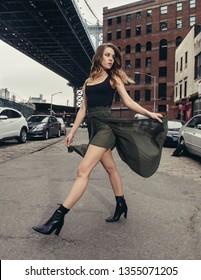 Stylish fashion model girl walking on city street wearing black top and green long sexy skirt