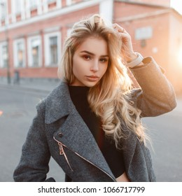 Stylish fashion model woman in fashionable gray jacket posing on the street at sunset