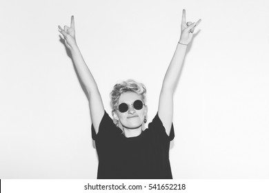 Stylish fashion sexy blonde bad girl in a black t-shirt and rock sunglasses. Dangerous rocky emotional woman giving the Rock and Roll sign, devil horns gesture. Black and white toned.