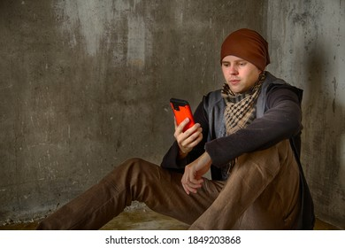 A stylish fashion tall young man in a brown hat, jeans and black mantle (robe) sits on the floor in a concrete room of an abandoned building and looks at the red smartphone screen. HDR image