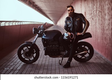 Stylish fashionable biker dressed in a black leather jacket with sunglasses holds a helmet sitting on his custom-made retro motorcycle, looking at camera.