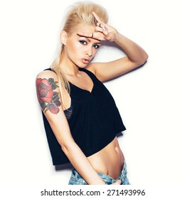 Stylish fashionable blonde girl hipster with tattoo in black clothes.  White background, not isolated