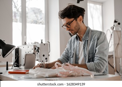 Stylish and fashionable clothes designer man sews at a sewing machine. Sewing, design work, tailoring studio, tailor, designer clothes, manufactory, in the process of creative development